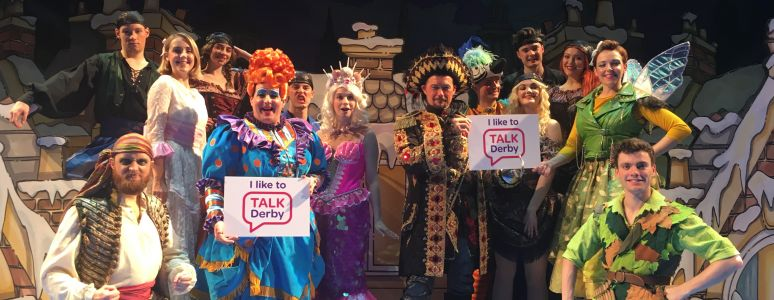 The cast of Peter Pan on stage at Derby Arena, wearing brightly coloured costumes and holding signs with Talk Derby printed on them
