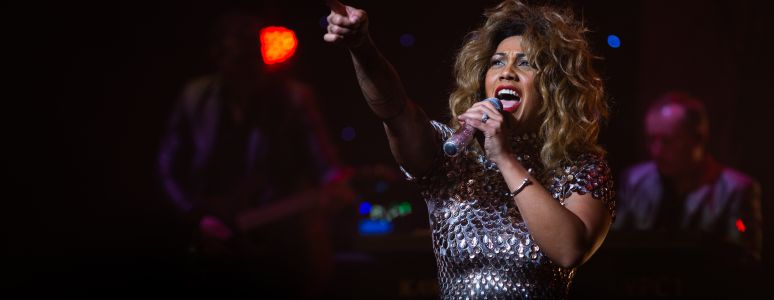 Actress as Tina Turner singing with band in dark background behind her