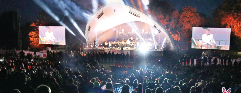 View of the half-circle shaped stage at Darley Park with big screens on each side. The background and the crowds in front are dark, and there are lights coming from the stage.